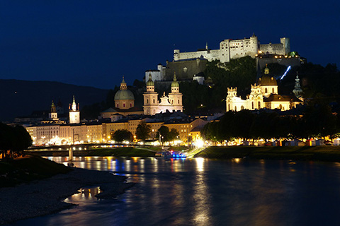 A large castle overlooks a city of multiple buildings nestled behind a river at night